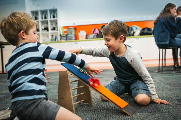 Two young boys racing toy cars down a ramp.