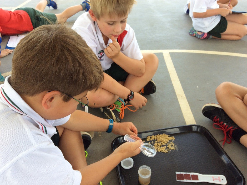 A group of students sitting outside and testing sand.