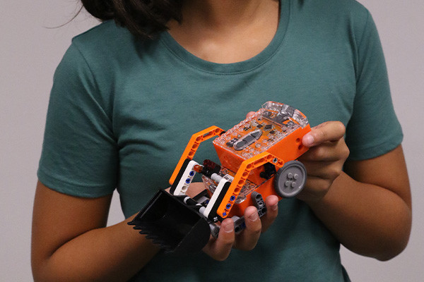 Close up of a person holding a small robotic digger.