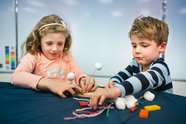 Two kids playing with arts & crafts materials.