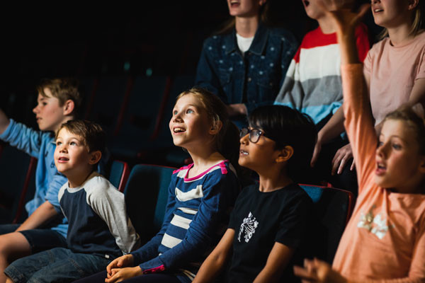 A group of young students watching a spacedome show, looking up and smiling.