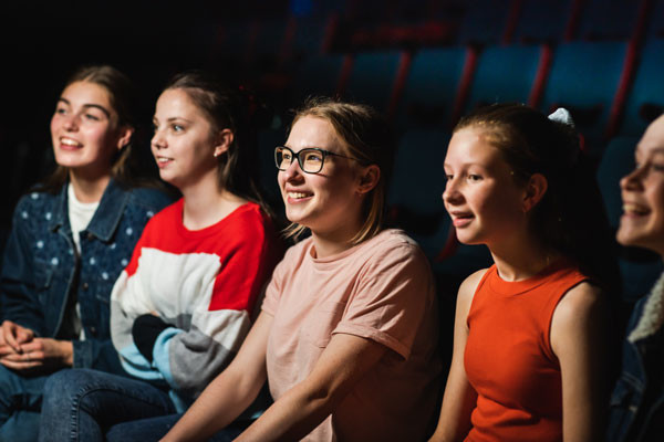 A group of girls watching a show, smiling and laughing.