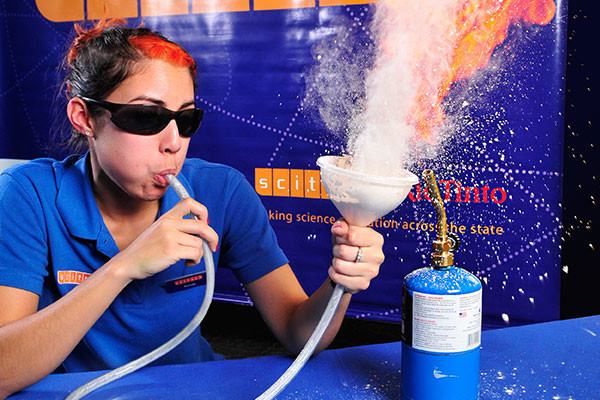 Science presenter blows coloured powder through a funnel.