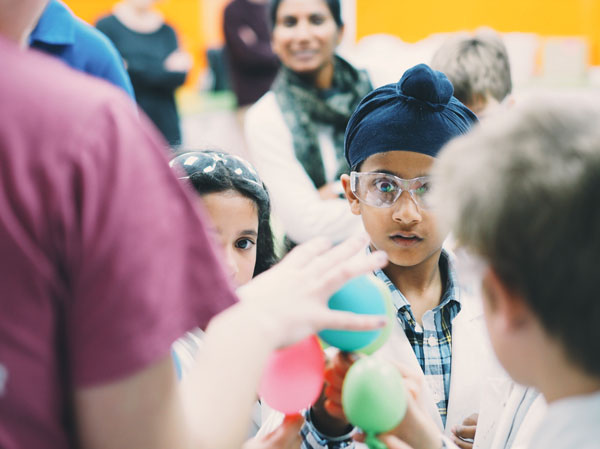 Young scientists looking excitedly at balloons.