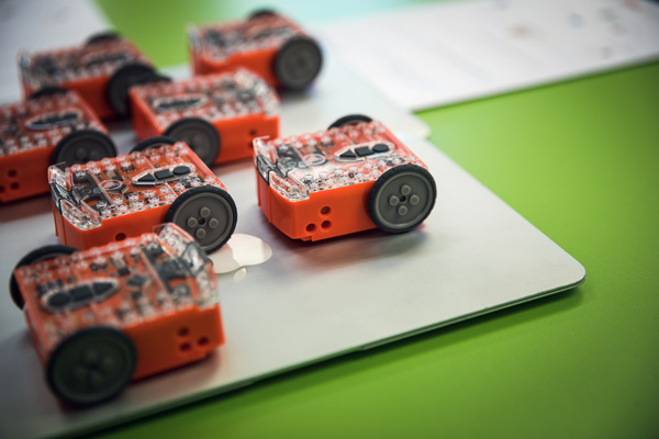 Close up of several small robotics devices, sitting on a laptop.