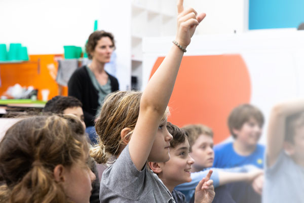 Students sitting in a classroom, with hands raised.