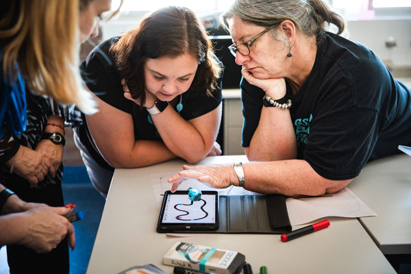 A group of teachers looking at an iPad and robot program on a desk.