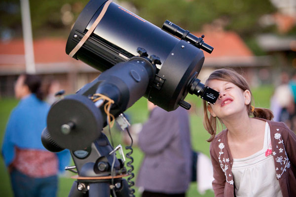Young girl looking through a large telescope.