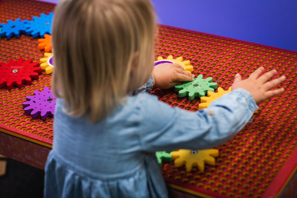 A young child plays with colourful cogs on a board.
