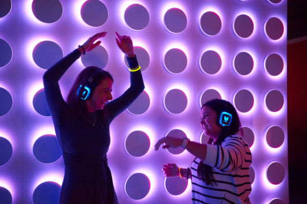 Two women wearing headphones and dancing at the After Dark silent disco.