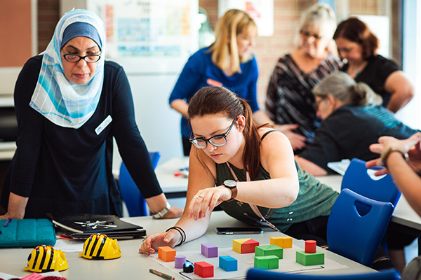 A group of teachers looking at robotics devices and coloured blocks on a table.