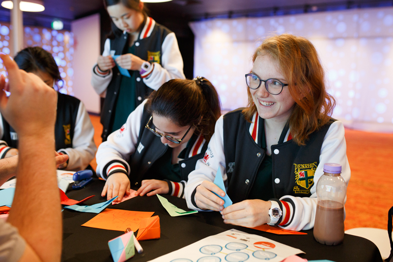 A group of high school students making origami objects.