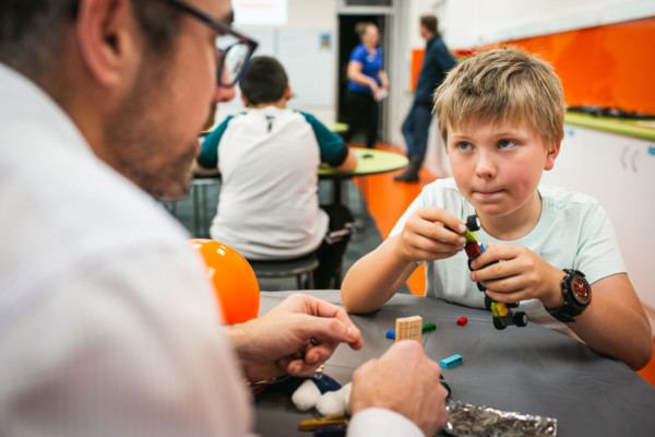 Young boy holding lego at an Investigating Engineers workshop.