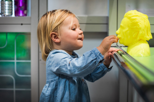 Young child touching a yellow, 3D printed model of Albert Einstein.