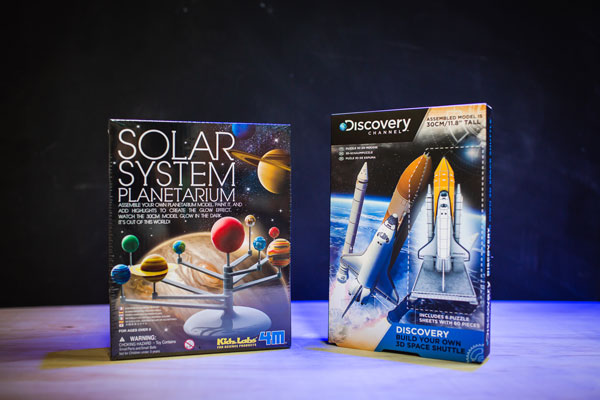 A solar system model toy and a rocket ship model toy, displayed in their boxes for The Discovery Shop.
