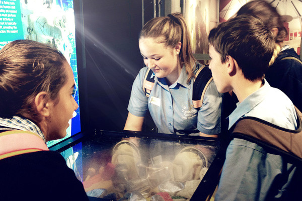 A group of students standing around a Scitech exhibit.