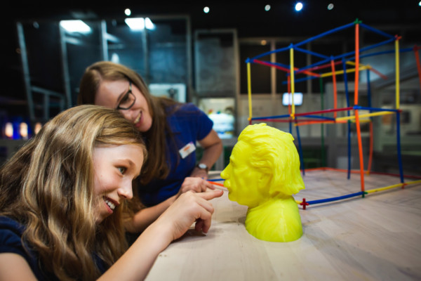 A girl looking at a yellow, 3D printed model of Albert Einstein