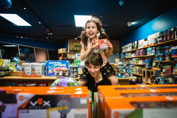 An older boy with a young girl on his shoulders, in the Discovery Shop.