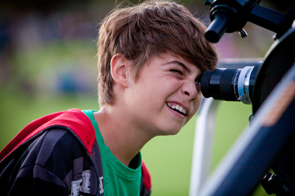 Young boy looks into telescope viewfinder.