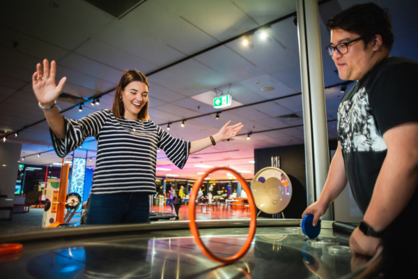 Two young adults play with a gravity exhibit