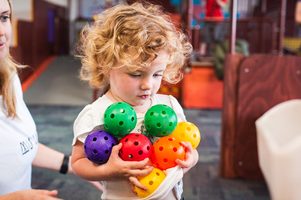 Young girl holding coloured plastic balls.