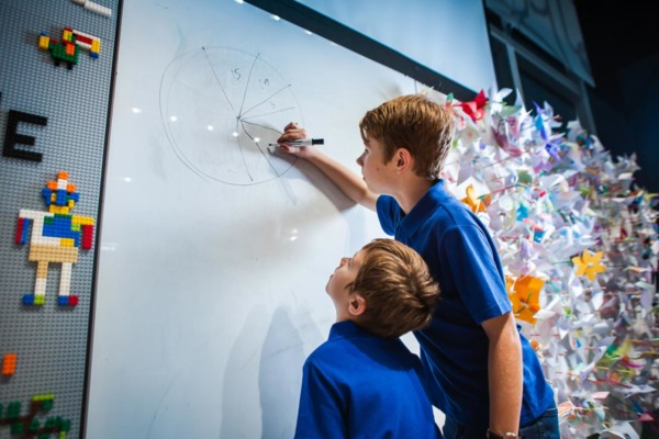 Two young students drawing a pie chart on a whiteboard.