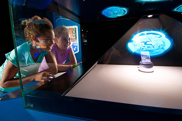 Two girl looking at an exhibit of a hologram.