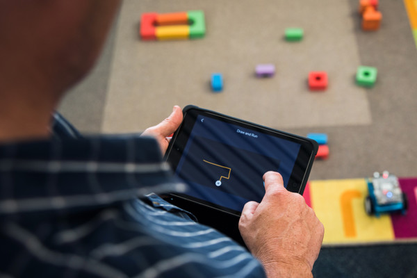 An adult holding an iPad at a workshop.