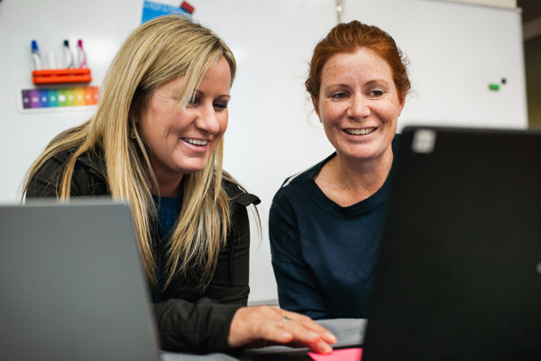 Two teachers smiling and looking at a laptop.