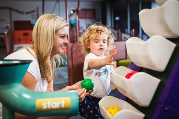 Woman and toddler playing in Discoverland with coloured plastic balls