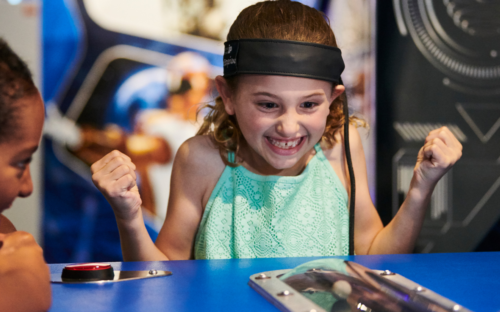 A girl cheering excitedly as she plays a game, she is wearing a band around her head and concentrating on the table in front of her.