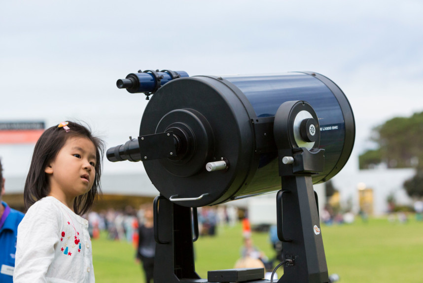 Girl looking through a telescope at astrofest.