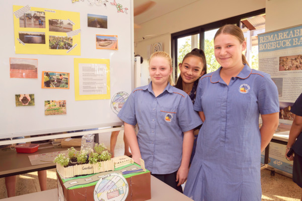 Students stand proudly with mini garden project in classroom