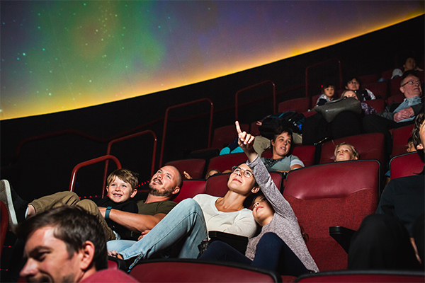 Adults and kids in the planetarium theatre, looking up at the screen.
