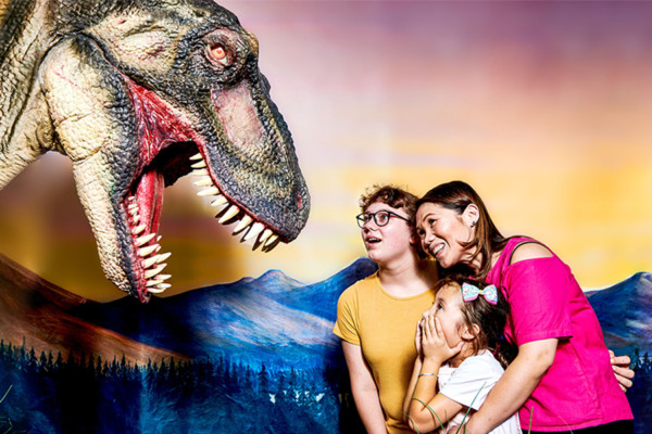 A woman and her two children looking up in amazement at an animatronic T-rex.