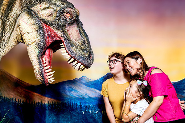 A Tyrannosaurus Rexroaring down at two young girls and their mum.