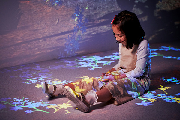 Girl sitting on floor looking at colourful projections over her legs