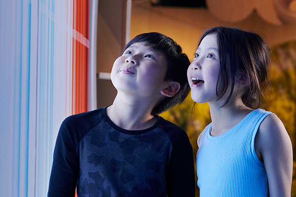 Boy and girl look up amazed at coloured wall