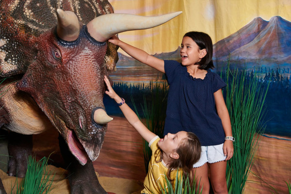 Two young girls patting an animatronic triceratops on the head,