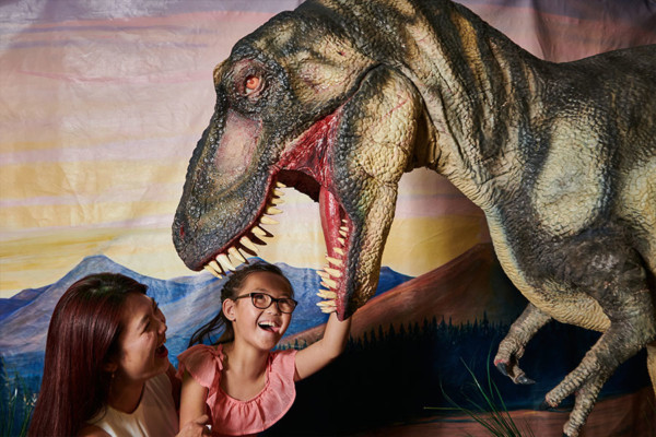A young girl and her mother smiling up at an animatronic Tyrannosaurus rex.