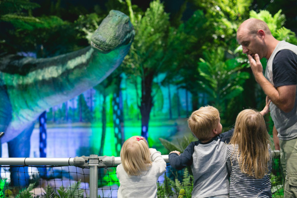 Man and three young children looking at an animatronic dinosaur display
