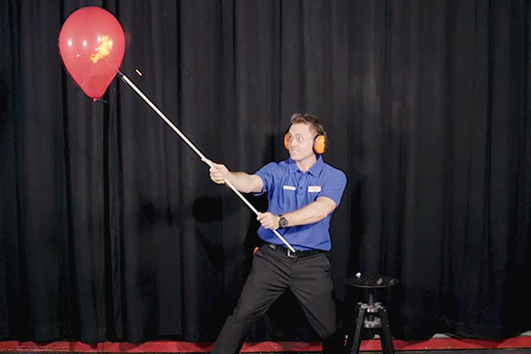 A scitech presenter holding a pole with a flame to a red balloon