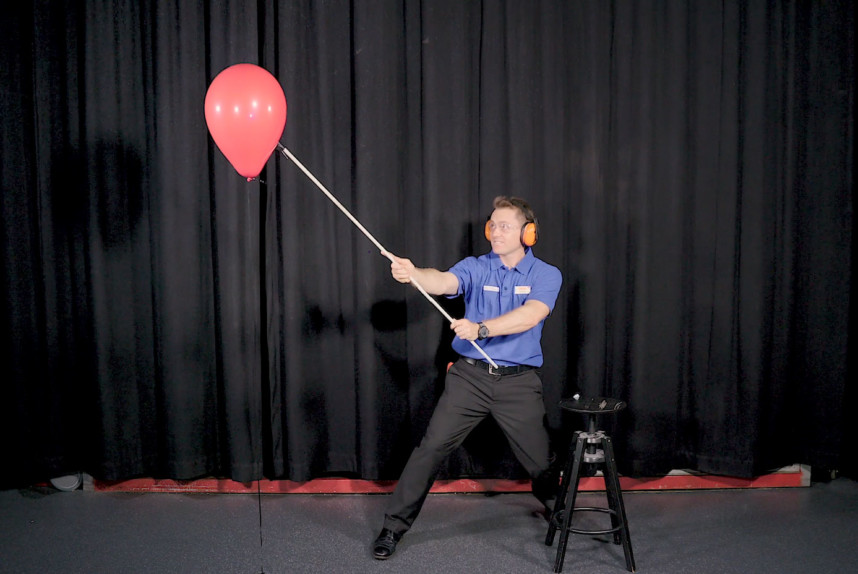 A man about to pop a red balloon with a flame on a stick.