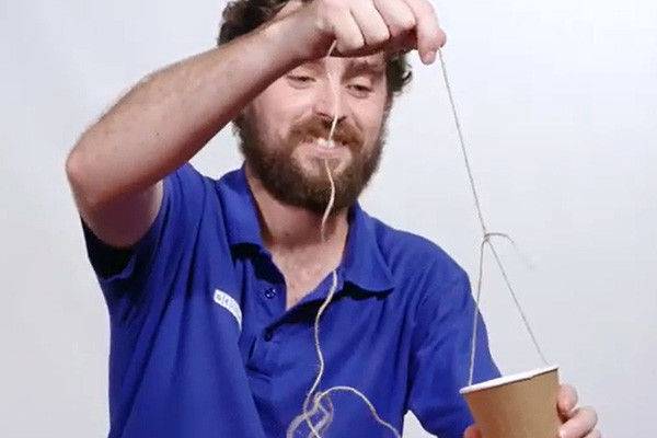 A man with a bright blue shirt with a cup with string around it.