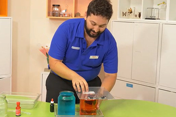 A man in a blue shirt holding a clipboard over a jar of red water next to a jar of blue water for an experiment.