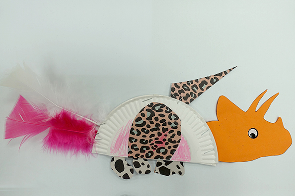 A Dinosaur made of purple feather and orange paper for a craft at home project.