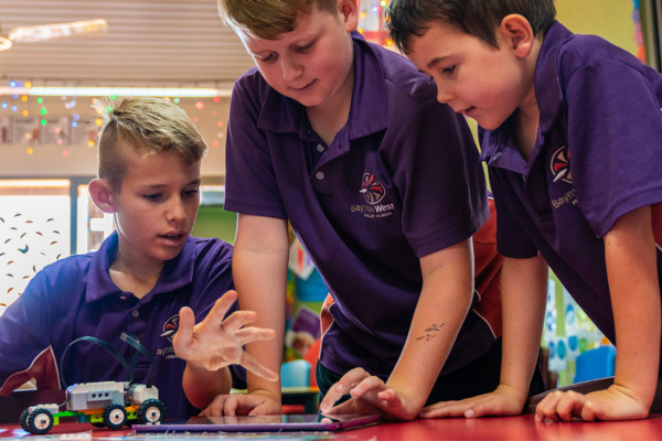 Three school aged boys learning standing around robotic toys.