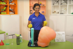 A scitech science presenter creating a reaction of coloured foam called elephants toothpaste.