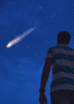 A young boy standing under the night sky looking up at a shooting star.