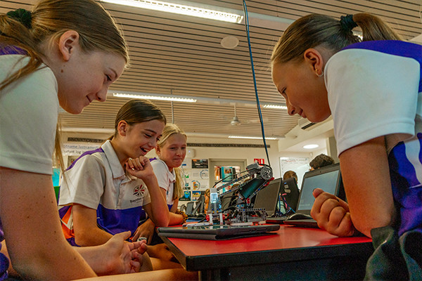 Three girls smiling while looking at a robotic toy.